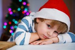 Kleiner Junge in Sankt-Hut mit Weihnachtsbaum und Lichtern Stockbild