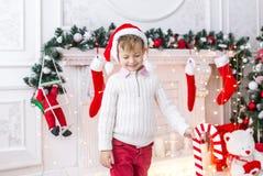 Kleiner Junge in Sankt-Hut träumt, ihren Kopf mit den Händen und den geschlossenen Augen stützend lizenzfreie stockfotografie