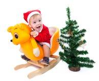 Kleiner Junge in Santa Claus-Klage, die eine Spielzeugkatze reitet Lizenzfreie Stockbilder