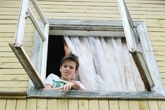 Kleiner Junge schaut aus dem alten Fenster heraus Lizenzfreies Stockfoto