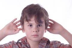 Kleiner Junge schließt Ohren Stockbild