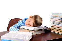 Kleiner Junge schlief auf Bücher ein Stockbild