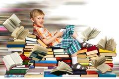 Kleiner Junge, schnelles Internet und ein Stapel von Büchern Stockfoto
