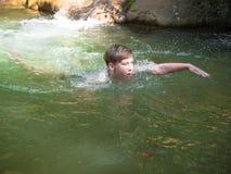 Kleiner Junge schwimmt auf die Oberfläche des Wassers Lizenzfreie Stockfotos