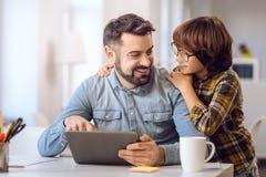 Kleiner Junge sehr, der glücklich auf seinem Vater schaut Lizenzfreies Stockfoto