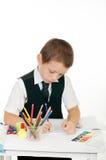 Kleiner Junge an seinem Schreibtisch mit einem Album für das Zeichnen, die Bleistifte und die Bücher auf weißem Hintergrund Stockfotos