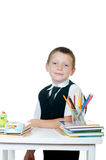 Kleiner Junge an seinem Schreibtisch mit einem Album für das Zeichnen, die Bleistifte und die Bücher auf weißem Hintergrund Lizenzfreie Stockfotografie