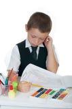 Kleiner Junge an seinem Schreibtisch mit einem Album für das Zeichnen, die Bleistifte und die Bücher auf weißem Hintergrund Lizenzfreies Stockbild