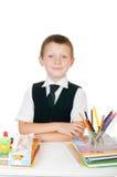 Kleiner Junge an seinem Schreibtisch mit einem Album für das Zeichnen, die Bleistifte und die Bücher auf weißem Hintergrund Stockfotografie