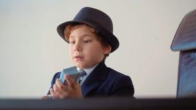 Kleiner Junge sieht wie Unternehmerzählungen die Gelddollar in seinem Büro aus stock video