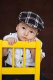 Kleiner Junge, sitzend auf einem Stuhl Stockbild
