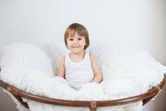 Kleiner Junge, sitzend in einem großen Stuhl Lizenzfreies Stockfoto