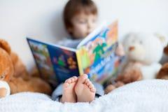 Kleiner Junge, sitzend im Bett und lesen ein Buch Stockbilder