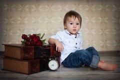 Kleiner Junge, sitzend nahe bei einer Uhr Lizenzfreies Stockfoto
