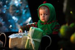 Kleiner Junge sitzt im Lehnsessel mit Weihnachtsgeschenken lizenzfreie stockbilder