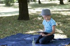 Kleiner Junge sitzt im Park und passt seinen Lieblingsvideoclip auf Lizenzfreie Stockfotografie