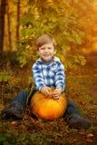 Kleiner Junge sitzt mit einem Kürbis und einem Lächeln Das Kind-enjo lizenzfreies stockbild
