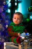 Kleiner Junge sitzt nahe Weihnachtsbaum und Geschenkboxen lizenzfreies stockbild