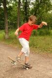 Kleiner Junge skateboard im Wald Stockbild