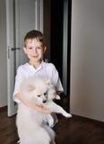 Kleiner Junge Smilinng 6-7 Jahre alte Holding der Hund Innen Stockfoto