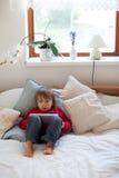 Kleiner Junge, spielend auf Tablette Stockfoto