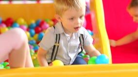 Kleiner Junge spielt auf Spielplatz mit Plastikbällen stock video footage