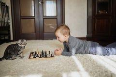 Kleiner Junge spielt das Schach, das auf Boden liegt Lizenzfreies Stockfoto