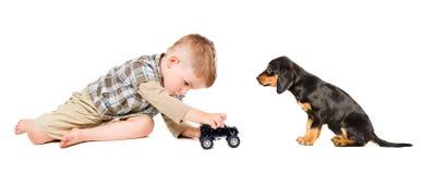 Kleiner Junge spielt ein Spielzeugauto mit seinem Welpen Stockfotos