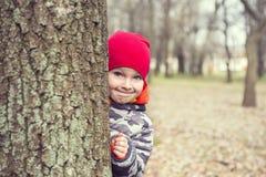 Kleiner Junge spielt Verstecken drau?en Portr?t eines netten kleinen Jungen, der von hinten Baum sp?ht lizenzfreie stockfotos