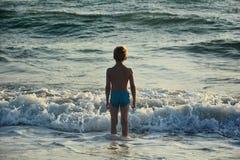 Kleiner Junge steht im Wasser vor einer Welle und schaut zum Meer Stockfotografie