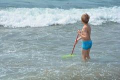 Kleiner Junge steht mit einem Fischernetz im Wasser Lizenzfreies Stockfoto