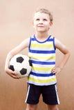 Kleiner Junge steht mit Fußball, Stockbild
