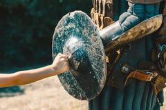 Kleiner Junge steht seine Faust auf dem Ritter still, gequetscht, geknackt, getragen stockbild