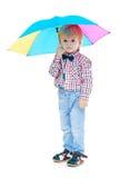 Kleiner Junge steht unter einem bunten Regenschirm Stockbild