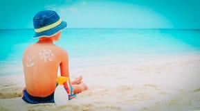 Kleiner Junge Sun-Schutzes mit suncream am Strand lizenzfreies stockfoto