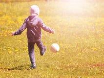 Kleiner Junge tritt einen Ball auf dem Gras stockbild