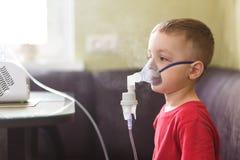 Kleiner Junge tut therapeutische Einatmung stockfotos
