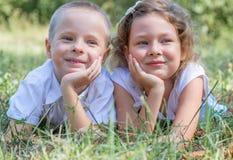 Kleiner Junge und das Mädchen liegen zusammen auf einem Gras Stockbilder