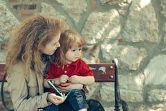 Kleiner Junge und Frau auf der Bank Lizenzfreies Stockfoto