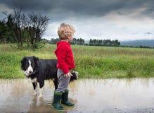 Kleiner Junge und Hund in der Pfütze Lizenzfreies Stockfoto