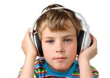 Kleiner Junge und im Kopfhörer setzt Hände auf ihn Lizenzfreie Stockbilder