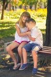 Kleiner Junge und kleines Mädchen, die im Park auf der Bank auf s spielt Stockfotografie