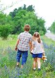 Kleiner Junge und kleines Mädchen mit dem Gehen Lizenzfreie Stockfotos