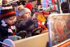 Kleiner Junge und Mädchen auf einem Karussell am Weihnachtsmarkt Lizenzfreie Stockfotos