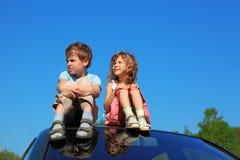 Kleiner Junge und Mädchen, die auf Autodach sitzt lizenzfreies stockbild