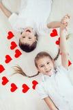 Kleiner Junge und Mädchen, die auf dem Boden liegt Stockbild