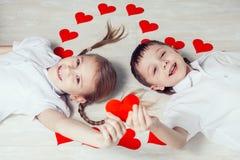 Kleiner Junge und Mädchen, die auf dem Boden liegt Lizenzfreies Stockbild