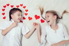 Kleiner Junge und Mädchen, die auf dem Boden liegt Stockbilder