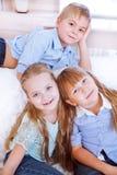 Kleiner Junge und Mädchen, die auf dem Sofa in dinning Raum sitzen stockfotos