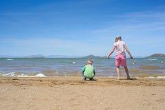 Kleiner Junge und Mädchen, die auf dem Strand spielt Stockbild